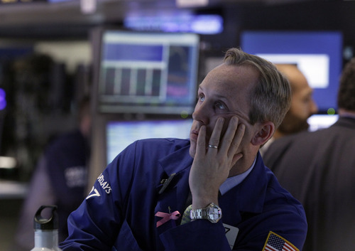 In this Monday, Oct. 22, 2012, photo, specialist Patrick Kenny works on the floor of the New York Stock Exchange. Stock futures are falling sharply Friday, Oct. 26, before the government provides a peek at the nation's economic growth over the past three months. Latest government data on the growth of the U.S. economy is expected to show tepid expansion. (AP Photo/Richard Drew)