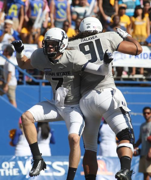 Utah State wide receiver Travis Van Leeuwen (7) celebrates his touchdown with teammate D.J. Tialavea (91) in the second quarter of an NCAA college football game in San Jose, Calif., Saturday, Oct. 13, 2012. (AP Photo/Darryl Bush)