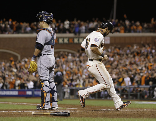 San Francisco Giants' Angel Pagan scores on a sacrifice fly by Hunter Pence during the eighth inning of Game 2 of baseball's World Series against the Detroit Tigers Thursday, Oct. 25, 2012, in San Francisco. Detroit Tigers' Gerald Laird is at left. (AP Photo/Marcio Jose Sanchez)