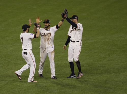 San Francisco Giants' Gregor Blanco, left, Angel Pagan, middle, and Hunter Pence celebrates after the Giants defeated the Detroit Tigers, 2-0, in Game 2 of baseball's World Series Thursday, Oct. 25, 2012, in San Francisco. (AP Photo/Jeff Chiu)