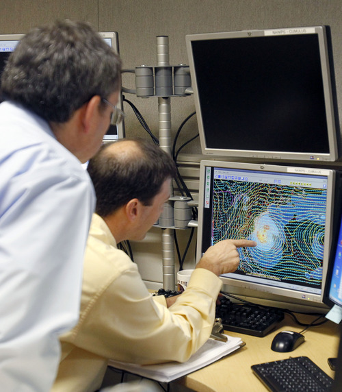 Senior hurricane specialist Dan Brown, right, points to a satellite image of Sandy to James Franklin, chief hurricane specialist, in preparation of the 11:00 EDT advisory at the National Hurricane Center in Miami, Saturday, Oct. 27, 2012. Early Saturday, the storm was about 335 miles southeast of Charleston, S.C. Tropical storm warnings were issued for parts of Florida's East Coast, along with parts of coastal North and South Carolina and the Bahamas. Tropical storm watches were issued for coastal Georgia and parts of South Carolina, along with parts of Florida and Bermuda. Sandy is projected to hit the Atlantic Coast early Tuesday. (AP Photo/Alan Diaz)