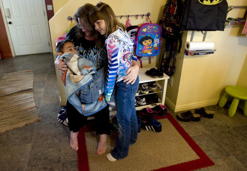 Kim Raff | The Salt Lake Tribune Happie Larson hugs (left) Marcel and Alyssa Larson, two children who were in foster care and were adopted by the Larsons, in their home in Layton Utah on October 24, 2012.  Happie Larson and her husband, Rich, have adopted 15 children from foster care, the last this June. They were able to get a tax credit that eased adoption expenses for four of the children. That tax credit will expire at the end of the year.