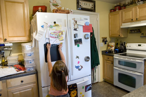 Kim Raff | The Salt Lake Tribune Piper Larson hangs a picture she colored on the fridge of her home.  Piper was in foster care and was adopted by Rich and his wife Happie earlier this year.