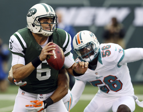 New York Jets' Mark Sanchez (6) is sacked by Miami Dolphins cornerback Jimmy Wilson (27) during the first half of an NFL football game Sunday, Oct. 28, 2012 in East Rutherford, N.J. (AP Photo/Seth Wenig)