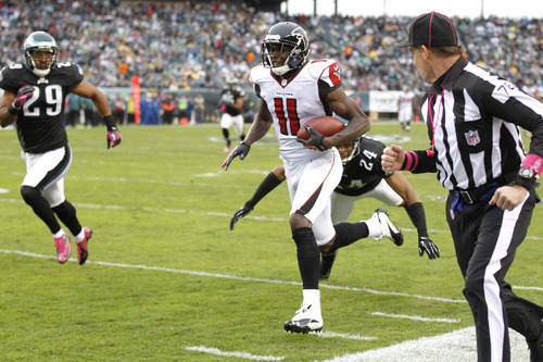 Atlanta Falcons wide receiver Julio Jones (11) scores on a 63-yard touchdown pass as Philadelphia Eagles cornerback Nnamdi Asomugha (24) goes in for the tackle during the first half of an NFL football game, Sunday, Oct. 28, 2012, in Philadelphia. (AP Photo/Mel Evans)