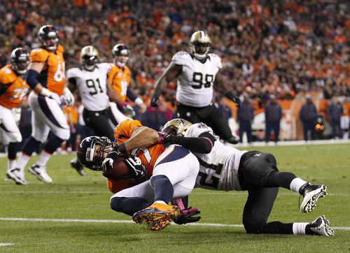 Denver Broncos wide receiver Eric Decker (87) comes down with a pass from quarterback Peyton Manning for a touchdown against New Orleans Saints cornerback Patrick Robinson (21) in the fourth quarter of an NFL football game, Sunday, Oct. 28, 2012, in Denver. (AP Photo/David Zalubowski)