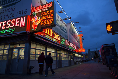 The facade of Nathan's Famous delicatessen glows against a cloudy sky near the Coney Island boardwalk in the Brooklyn borough of New York Sunday, Oct. 28, 2012, as the outer bands of Hurricane Sandy spread over the Northeast Coast. Coney Island and other New York City neighborhoods were under a mandatory evacuation order as the city braced for the arrival of the hurricane and a possible flooding storm surge. (AP Photo/Craig Ruttle)