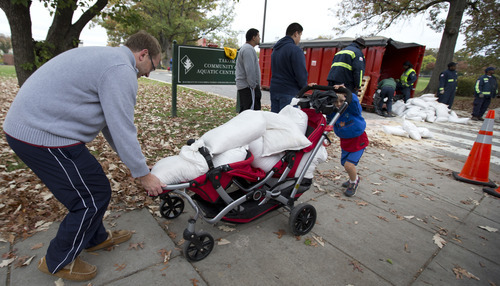 Mark Silverman, left, and his son Alexander, 4, push a baby carrier loaded with sandbags handed out for free by District of Columbia Department of Public Works workers, Sunday, Oct. 28, 2012.  (AP Photo/Manuel Balce Ceneta)