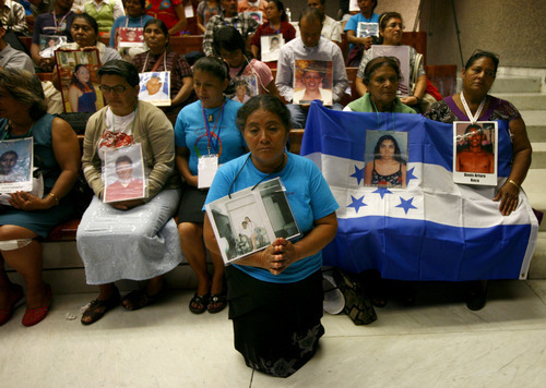 Members of a caravan of Central American mothers, some holding a Honduran flag, hold photographs of their disappeared children during a mass at the Basilica of Guadalupe in Mexico City, Sunday, Oct. 28, 2012. The convoy, mostly comprised of women from Central America, travels through Mexico to search for their relatives who left for a better life and then disappeared on their journey to the U.S. About 100 have been reunited through similar trips through Mexico over six years. (AP Photo/Marco Ugarte)