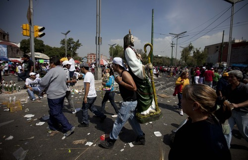 Jonathan Cepeda carries a statue of Saint Jude, the Catholic saint of lost causes, on the surroundings of the church of San Hipolito in Mexico City Sunday, Oct. 28, 2012. Thousands flocked to the church of San Hipolito as part of an annual pilgrimage honoring Saint Jude. (AP Photo/Eduardo Verdugo)