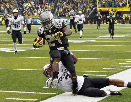 Oregon running back Kenjon Barner (24) is dragged out of bounds by Colorado defender Ray Polk during the first half of an NCAA college football game in Eugene, Ore., Saturday, Oct. 27, 2012. (AP Photo/Don Ryan)