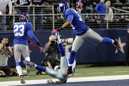 Sharon Ellman | The Associated Press Dallas' Dez Bryant hauls in a catch between the Giants' Cory Webster, left, and Michael Coe late in the fourth quarter. Initially called a touchdown, Bryant was ruled out of bounds and the Cowboys lost.