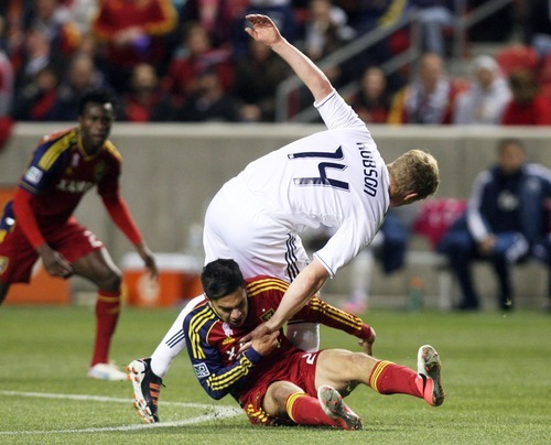 Kim Raff | The Salt Lake Tribune Real Salt Lake player David Viana (25) tries to pull Vancouver FC midfielder Barry Robson (14) down to the ground during a game at Rio Tinto Stadium in Sandy, Utah on October 27, 2012.