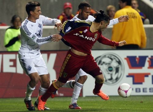 Kim Raff | The Salt Lake Tribune Real Salt Lake forward Fabian Espindola (7) is held back from the ball by Vancouver FC defender Alain Rochat (4) during a game at Rio Tinto Stadium in Sandy, Utah on October 27, 2012.