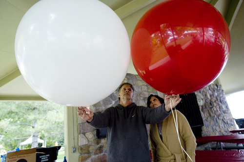 Kim Raff | The Salt Lake Tribune (left) Steve and Kristi Nielsen fill large balloons with air for decorating  the Leukemia and Lymphoma Society's Light the Night Walk at Sugarhouse Park in Salt Lake City on Saturday, October 13, 2012. They are the owners of Balloon Bonanza and now use more air-filled balloons for events of because of the national shortage of helium.