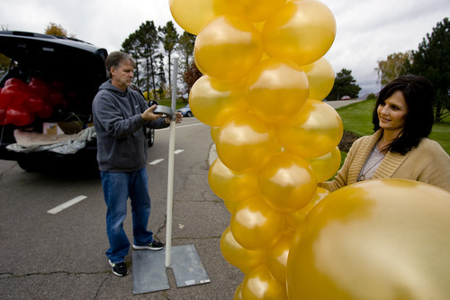 Kim Raff | The Salt Lake Tribune Kristi Nielsen holds a columns of air-filled balloons as her husband Steve sets up a support before the Leukemia and Lymphoma Society's Light the Night Walk at Sugarhouse Park in Salt Lake City on Saturday, October 13, 2012. Kristi and her husband Steve, owners of Balloon Bonanza, now use more air-filled balloons for events of because of the national shortage of helium.