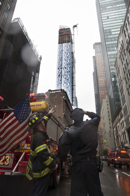 A FDNY firefighter and a New York police officer look up at a construction crane atop a luxury high-rise dangling precariously over the streets after collapsing in high winds from Hurricane Sandy, Monday, Oct. 29, 2012, in New York. Hurricane Sandy bore down on the Eastern Seaboard's largest cities Monday, forcing the shutdown of mass transit, schools and financial markets, sending coastal residents fleeing, and threatening a dangerous mix of high winds, soaking rain and a surging wall of water up to 11 feet tall. (AP Photo/John Minchillo)