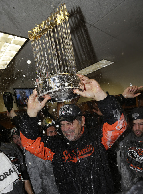 San Francisco Giants manager Bruce Bochy hold the Commissioner's Trophy after Game 4 of baseball's World Series against the Detroit Tigers Monday, Oct. 29, 2012, in Detroit. The Giants won the game, 4-3, to win the series. (AP Photo/David J. Phillip)