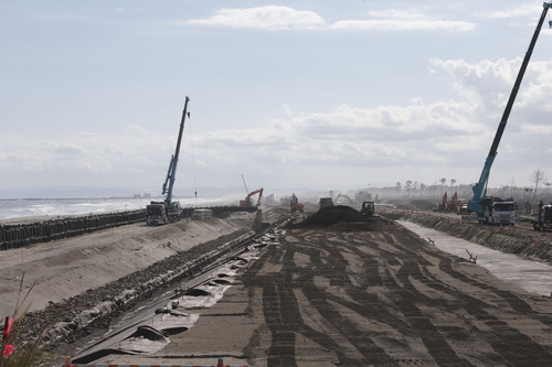 In this Oct. 9, 2012 photo, construction works go on along the Arahama beach, severely damaged by the March 11, 2011 earthquake and tsunami, in Sendai, northeastern Japan. Japan's accounting of its budget for reconstruction from the disasters is crammed with spending on unrelated projects, while all along Japan's northeastern coast, dozens of communities remain uncertain of whether, when and how they will rebuild. (AP Photo/Koji Sasahara)