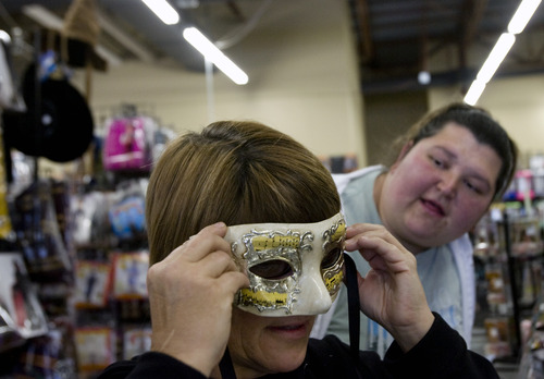 Kim Raff   The Salt Lake Tribune Wendy Chamberlain tries on a mask as (right) Sarah Orn looks on at Mask Costumes in Taylorsville on Oct. 25, 2012.