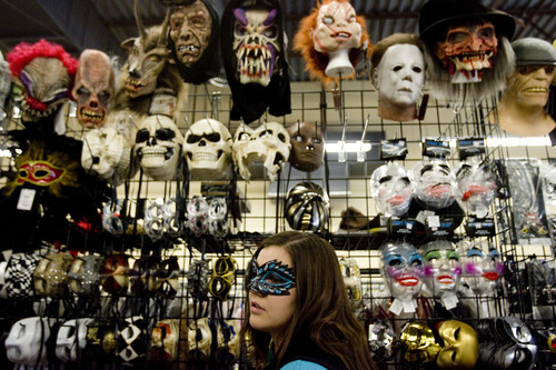 Kim Raff   The Salt Lake Tribune Tegan Storrs, shop sales woman, helps customers try on masks at Mask Costumes in Taylorsville on Oct. 25, 2012.