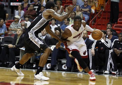 Miami Heat's Dwyane Wade (3) drives around San Antonio Spurs' Kawhi Leonard during the first half of an NBA basketball game in Miami, Saturday, Oct. 20, 2012. (AP Photo/J Pat Carter)