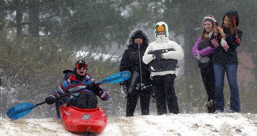 """Brannen Hinerman, 19, left, of Statesville, gets ready to pilot his kayak down """"suicide hill"""" on the campus of Appalachian State University in Boone, N.C. Tuesday Oct. 30, 2012. The North Carolina mountains got a taste of winter as superstorm Sandy brought high winds, freezing temperatures and several inches of snow to the mountains. (AP Photo/The News & Observer, Chuck Liddy) MANDATORY CREDIT"""