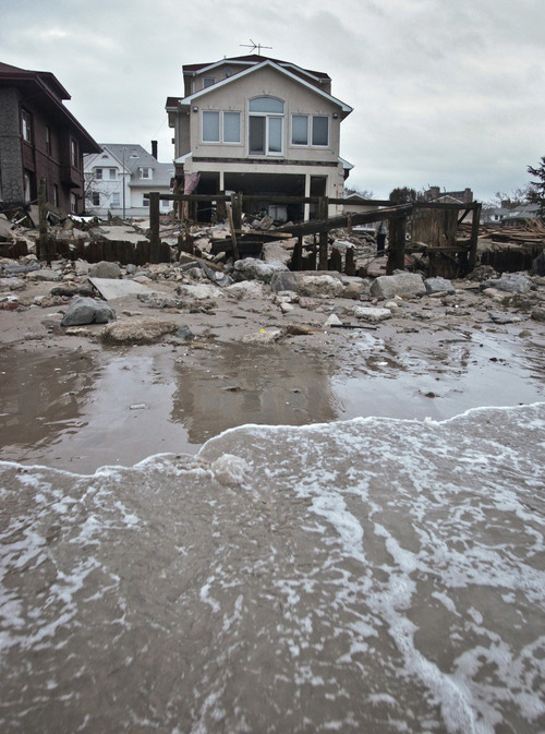 A beachfront house is damaged in the aftermath of yesterday's storm surge from Hurricane Sandy, Tuesday, Oct. 30, 2012, in Coney Island's Sea Gate community in New York.   (AP Photo/Bebeto Matthews)