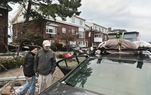 Thomas Andrews, right, with the help of his son Peter Andrews, prepare to leave his beachfront home with his belongings in the aftermath of Hurricane Sandy, Tuesday, Oct. 30, 2012, in Coney Island's Sea Gate community in New York.  Andrews, 85, a physicist,  moved into the house in1970 raising two sons.  Andrews said they had just found a buyer for the house.  (AP Photo/Bebeto Matthews)