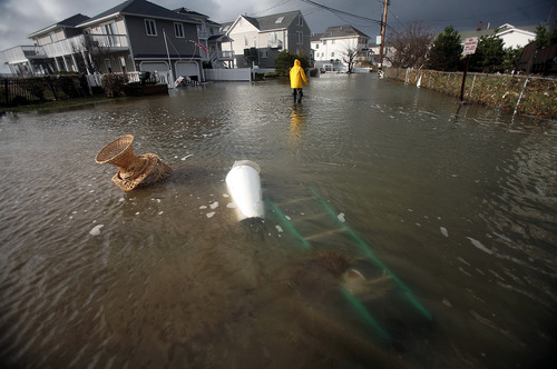 A man walks through floodwaters in the aftermath of Sandy on Tuesday, Oct. 30, 2012, in Milford, Conn. Sandy, the storm that made landfall Monday, caused multiple fatalities, halted mass transit and cut power to more than 6 million homes and businesses. (AP Photo/The Connecticut Post, Brian A. Pounds) MANDATORY CREDIT