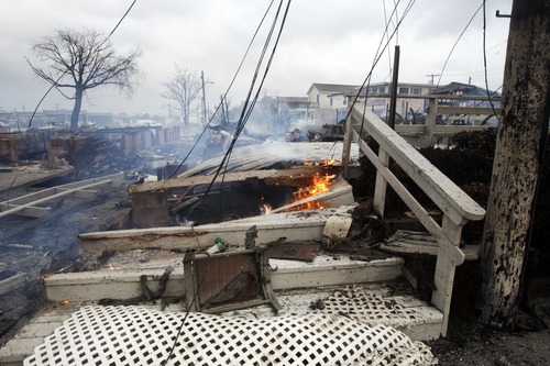 Fire still burns at the scene of a fire in Breezy Point, in the New York City borough of Queens Tuesday, Oct. 30, 2012, in New York. The fire destroyed between 80 and 100 houses Monday night in the flooded neighborhood. More than 190 firefighters have contained the six-alarm blaze fire, but they are still putting out some pockets of fire. (AP Photo/Frank Franklin II)