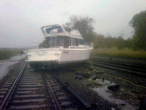 This photo provided by the Metropolitan Transportation Authority of the State of New York shows a boat resting on the tracks at Metro-North's Ossining Station in the aftermath of Hurricane Sandy on Tuesday, Oct. 30, 2012, in Ossining,N.Y. Sandy, the storm which was downgraded from a hurricane just before making landfall, caused multiple fatalities, halted mass transit and cut power to more than 6 million homes and businesses. (AP Photo/Metropolitan Transportation Authority of the State of New York) MANDATORY CREDIT