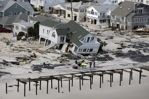 In this aerial photo, people survey destruction left in the wake of superstorm Sandy, Wednesday, Oct. 31, 2012, in Seaside Heights, N.J. (AP Photo/Mike Groll)