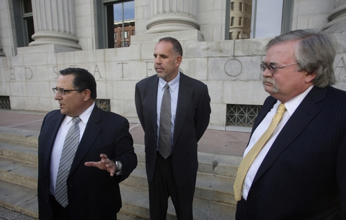 """Retired FBI agent Robert G. Lustyik Jr., center, stands with his attorneys Raymond Mansolillo, left, and J. Michael Hansen, after a federal court hearing in Salt Lake City on Tuesday, Oct. 30, 2012. Lustyik pleaded not guilty to charges of trying to derail an investigation into a defense contract scandal in exchange for promises of riches that apparently never materialized. Prosecutors say he was a counterintelligence officer based in White Plains, N.Y., who agreed to """"blow the doors off"""" a federal investigation for a share in the business of Boston-based American International Security Corp., a defense and security firm. (AP Photo/Rick Bowmer)"""