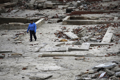 A woman walks past the remains of buildings in the wake from superstorm Sandy, Wednesday, Oct. 31, 2012, in Atlantic City, N.J. Sandy was being blamed for at least six deaths across the state plus power outages that at their peak Monday affected 2.7 million residential and commercial customers. (AP Photo/Matt Slocum)