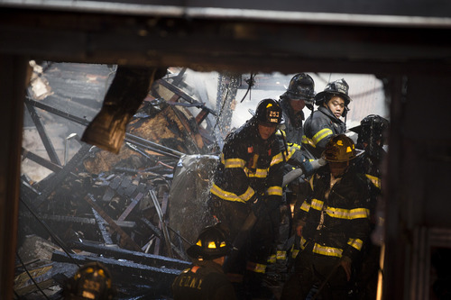 FDNY firefighters respond to a fire in a storefront after the roof collapsed, Wednesday, Oct. 31, 2012, in the Brooklyn borough of New York. Sandy, the storm that made landfall Monday, caused multiple fatalities, halted mass transit and cut power to more than 6 million homes and businesses. (AP Photo/ John Minchillo)