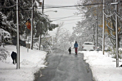 A few pedestrians walk on t a snow cleared street in Fayettville  W.Va., Tuesday, Oct. 30, 2012 after superstorm Sandy dumped 2 feet of snow in parts of the West Virginia mountains by Tuesday afternoon.  Drifts 4 feet deep were reported at Great Smoky Mountains National Park on the Tennessee-North Carolina border. (AP Photo/Charleston Daily Mail, Tom Hindman)