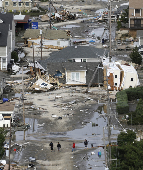 In this aerial photo, people walk amid the destruction left in the wake of superstorm Sandy, Wednesday, Oct. 31, 2012, in Seaside Heights, N.J. (AP Photo/Mike Groll)