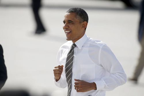 President Barack Obama jogs on the tarmac upon his arrival, on Air Force One, at McCarran International Airport, for a campaign event, Thursday, Nov. 1, 2012, in Las Vegas. (AP Photo/Isaac Brekken)