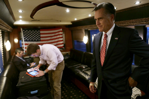 Republican presidential candidate, former Massachusetts Gov. Mitt Romney holds on in the back of his campaign bus with aide Garrett Jackson, center, and senior adviser Kevin Madden, left, after a campaigning at Meadow Event Park in Richmond, Va., Thursday, Nov. 1, 2012. (AP Photo/Charles Dharapak)