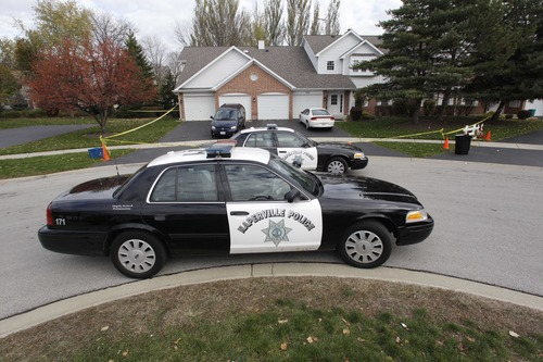 Police cars are seen outside a home in Naperville, Ill., Thursday, Nov. 1, 2012, where two children were founded stabbed to death on Tuesday, Oct. 30. Elzbieta Plackowska, 40, was charged with first-degree murder and denied bond at a hearing Thursday in Wheaton, Ill. Prosecutiors said Thursday that Plackowska stabbed her 7-year-old son 100 times because she was angry with her husband and a 5-year-old girl about 50 times because she witnessed the attack, as both children prayed and begged for their lives. (AP Photo/M. Spencer Green)