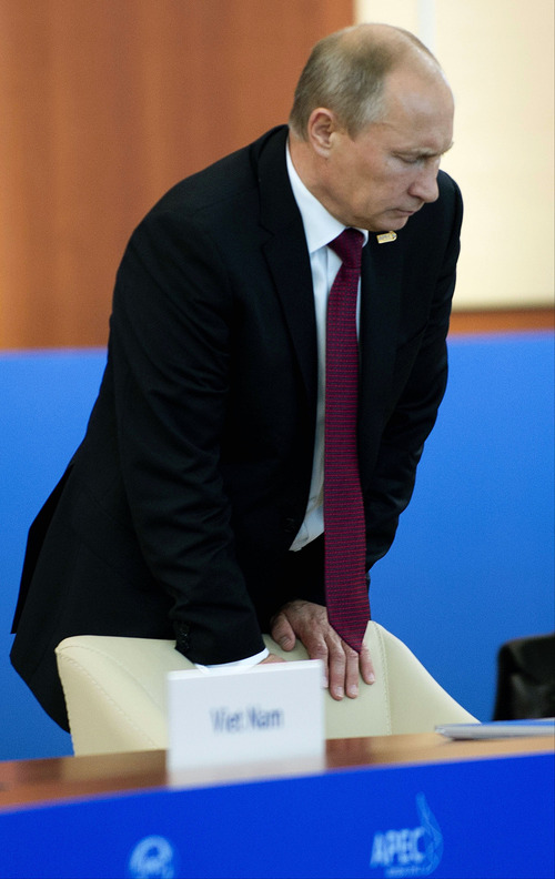 "FILE - In this Sunday, Sept. 9, 2012, file pool photo, Russian President Vladimir Putin braces himself against his chair as he arrives to begin the Asia-Pacific Economic Cooperation (APEC) Summit Leaders Retreat II in Vladivostok, Russia, on Sunday, Sept. 9, 2012. On Thursday, Nov. 1, 2012, Interfax reported that Putin's spokesman Dmitry Peskov said the president had pulled a muscle. ""It happened before Vladivostok. He was suffering from muscle pain then"", Peskov said. Peskov told state news agency RIA Novosti this was an old injury and denied it was caused by his flight with cranes.   (AP Photo/Jim Watson, Pool, File)"