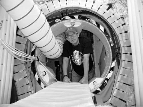 In this Wednesday, Oct. 3, 2012 photo, shuttle technician Joe Walsh looks through a hatch of the space shuttle Atlantis at the Kennedy Space Center in Cape Canaveral, Fla. Atlantis isn't going far to its retirement home at Kennedy Space Center's main tourist stop. But it might as well be a world away for the workers who spent decades doting on Atlantis and NASA's other shuttles. Those who agreed to stay until the end - and help with the shuttles' transition from round-the-world flying marvels to museum showpieces - now face unemployment just as so many of their colleagues did over the last few years. (AP Photo/Marcia Dunn)