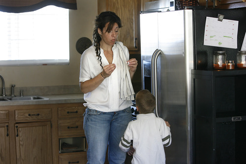 """Scott Sommerdorf     The Salt Lake Tribune               Nicole VanBuskirk tries to get her 6-year-old son, Austin, who is autistic, to sign """"more"""" before she gives him a vogurt cup. Austin works with therapist Breanne Berg who teaches an autism therapy like the one covered in the state-funded pilot, Monday, October 29, 2012."""