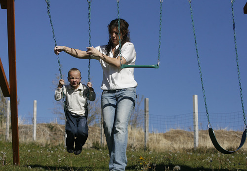 Scott Sommerdorf     The Salt Lake Tribune               Nicole VanBuskirk helps her 6-year-old autistic son, Austin, swing in the family's backyard. Austin works with Breanne Berg who teaches an autism therapy like the one covered in the state-funded pilot, Monday, October 29, 2012.