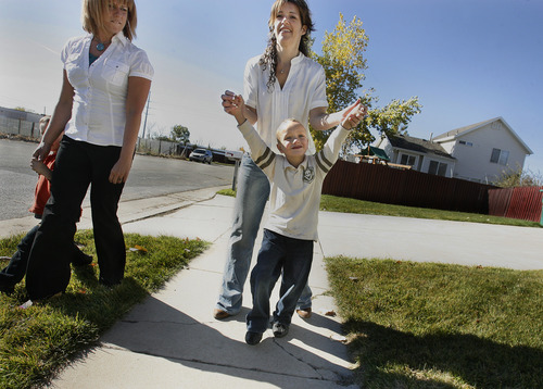 Scott Sommerdorf  |  The Salt Lake Tribune               Nicole VanBuskirk, right, walks with her 6-year-old autistic son, Austin, while on a walk with therapist Breanne Berg, left. Berg is holding VanBuskirk's other son, Trevor. Berg teaches an autism therapy like the one covered in the state-funded pilot, Monday, October 29, 2012.