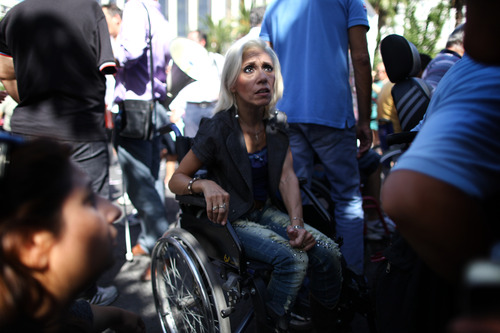 FILE - In this Sept. 27, 2012, file photo, Anastasia Mouzakiti, center, a paraplegic, came to the demonstration from the northern city of Thessaloniki with her husband, to protest outside the Greek parliament. To the casual visitor, all might appear well in Athens, but scratch the surface and you find a society in freefall, ripped apart by the most vicious financial crisis the country has seen in half a century. (AP Photo/Petros Giannakouris)