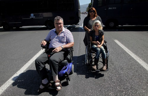 FILE In this Thursday, Sept. 27, 2012 file photo, Anastasia Mouzakiti, right, a paraplegic from the northern city of Thessaloniki, who came to Athens with her husband, left, who is also handicapped, to demonstrate, depart from a protest, outside the Greek parliament. To the casual visitor, all might appear well in Athens. But scratch the surface and you find a society in freefall, ripped apart by the most vicious financial crisis the country has seen in half a century. (AP Photo/Petros Giannakouris)