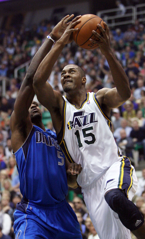 Steve Griffin | The Salt Lake Tribune   Utah's Derrick Favors gets past Dallas' Bernard James during first-half action of theseason opener against Dallas at EnergySolutions Arena  in Salt Lake City on Wednesday, Oct. 31, 2012.