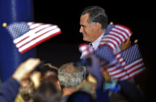 Republican presidential candidate, former Massachusetts Gov. Mitt Romney walks offstage amid waving American flags during a campaign event at Metropolitan Park, Wednesday, Oct. 31, 2012, in Jacksonville, Fla. (AP Photo/Rick Wilson)
